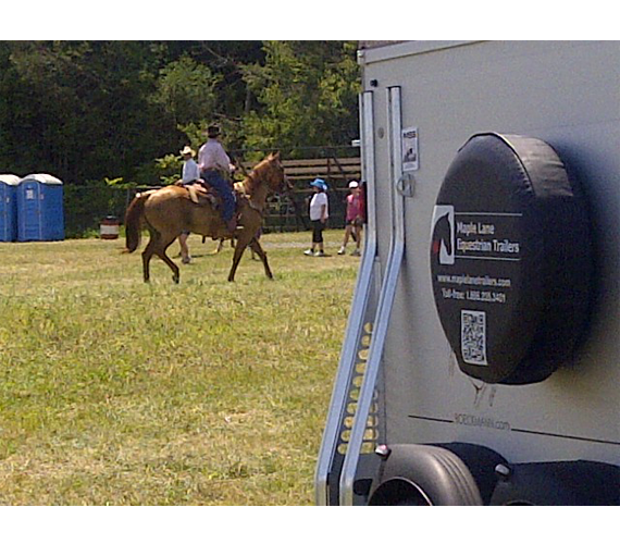 Cowboy riding horse by trailer at the Rodeo